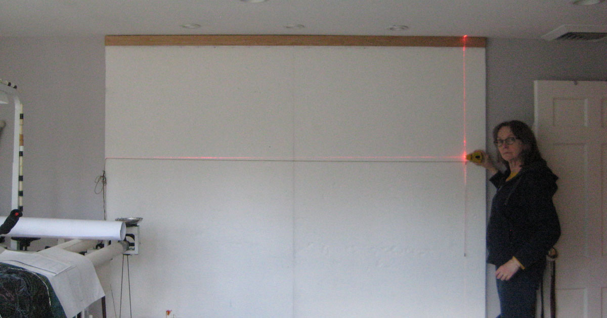 Artist Susan Polansky using a laser level in the art studio